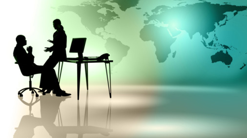 Silhouettes of business people at desk with world map